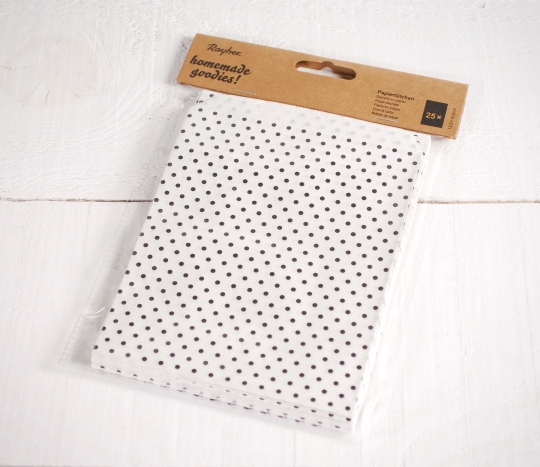 Sacs en papier blancs avec des pois noirs